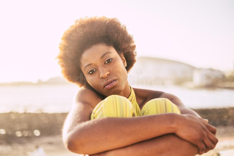 Beautiful skin and face for nice blacj race african model with alternative afro hair. sad and lonely hugging herself at the beach. With defocused ocean in royalty free stock image
