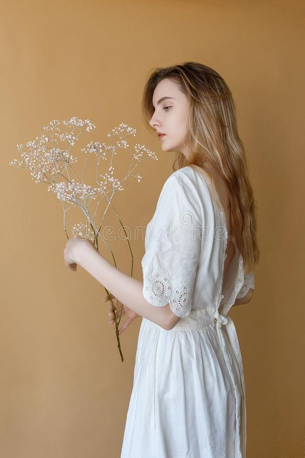 Beautiful skinny young girl with long hair in white dress on beige background holding white flowers in her hands royalty free stock images