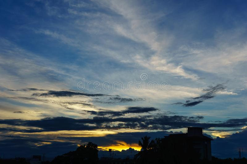 beautiful sky and cloud when sunset over city. silhouette of town when sunset at dusk with dramatic twilight sun light over sky stock images