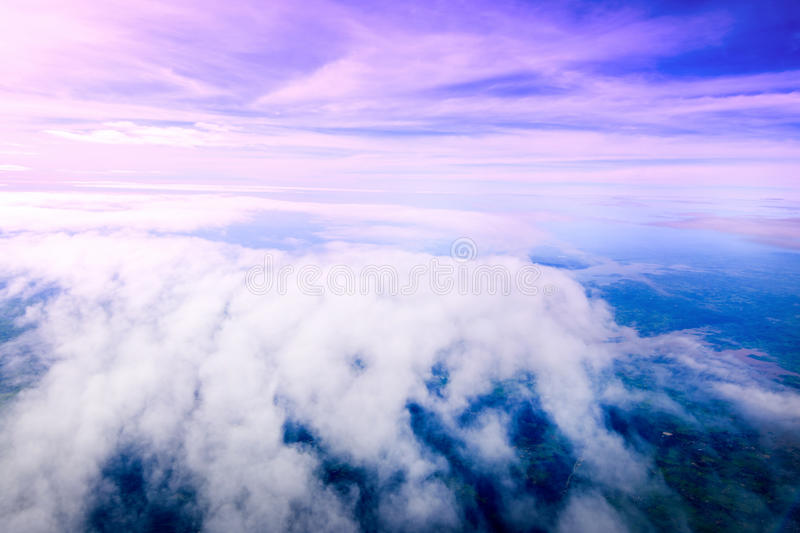 Beautiful sky clouds. Seeing through the airplane windows. Sunset aerial view through airplane window over wings royalty free stock photos
