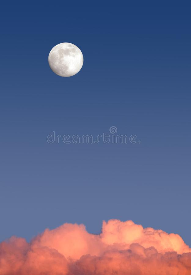 Beautiful sky landscape with white full moon high on clear blue gradient sky above red clouds on sunset stock photo