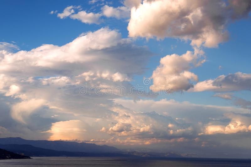Beautiful sky sunset with clouds during golden hour over ocean shore royalty free stock photos