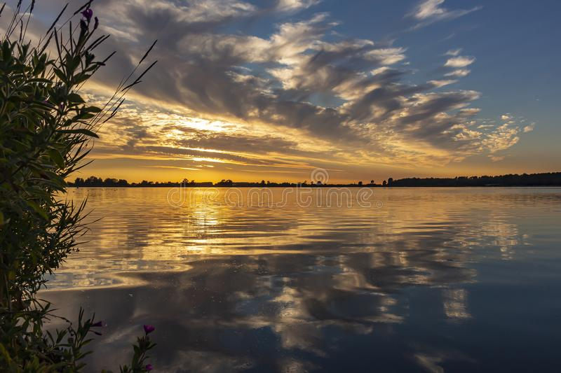 The beautiful sky is during sunset reflected in lake Zoetermeerse Plas, Netherlands.  stock photos