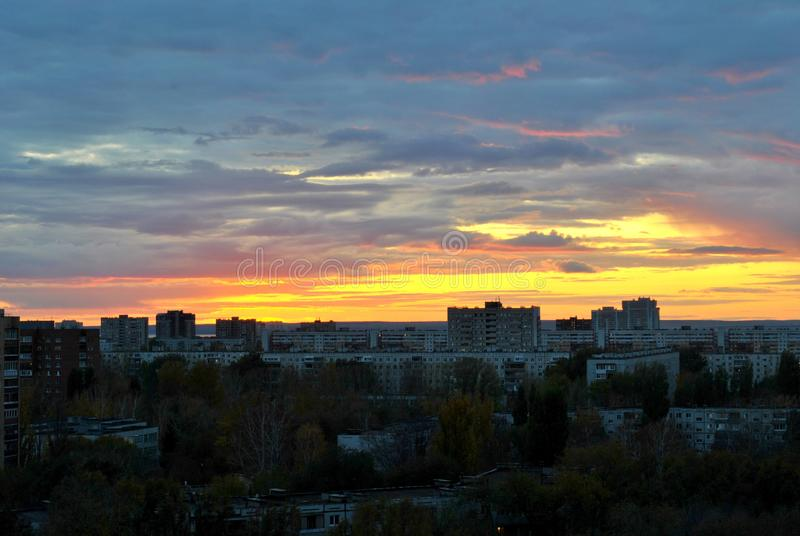 Beautiful sky and sunset tinted clouds over the evening panorama of the city. royalty free stock images