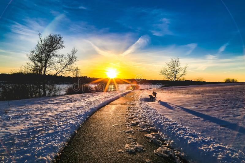 Sunset with beautiful skyline over lake Zorinsky Omaha Nebraska. Beautiful skyline at dusk /sunset over lake Zorinsky in winter Omaha Nebraska USA. Snow on the royalty free stock image