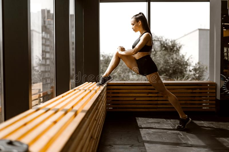 Beautiful slander girl dressed in black sports top and shorts is doing stretching on a wooden window sill in the gym.  royalty free stock image