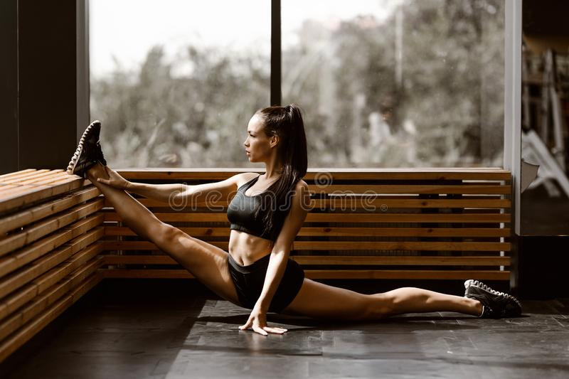 Beautiful slander girl dressed in black sports top and shorts is doing stretching on a wooden window sill in the gym.  royalty free stock images