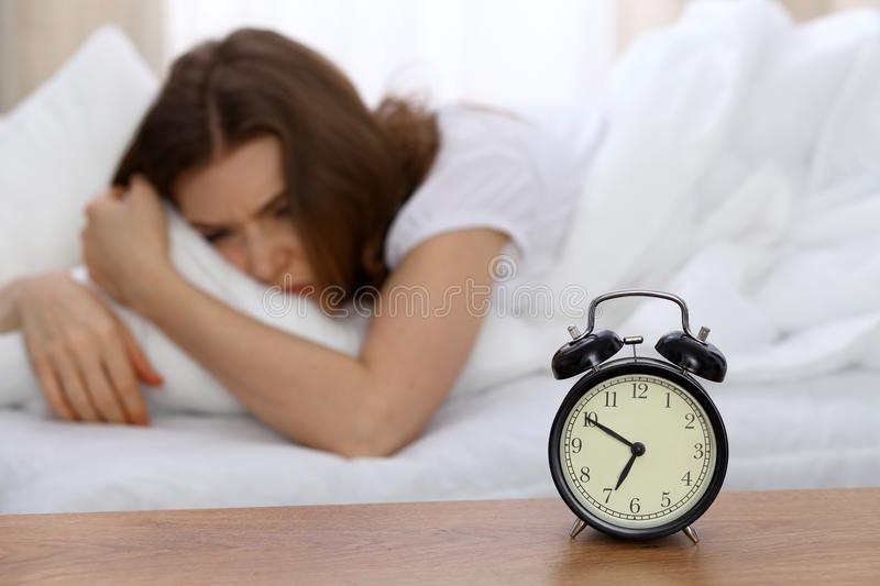 Beautiful sleeping woman lying in bed and trying to wake up with alarm clock. Girl having trouble with getting up early royalty free stock photos