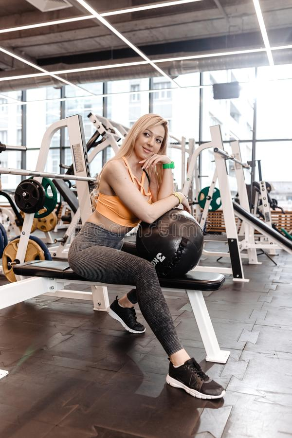 Beautiful slender blond girl with long hair dressed in a sportswear is sitting with the fitness ball on the bench in the royalty free stock image