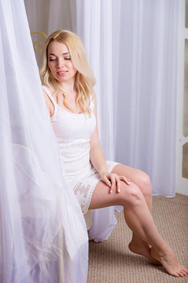 Beautiful slender blond girl posing on bed royalty free stock photos
