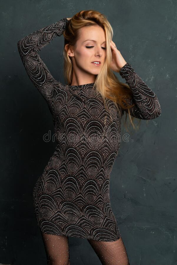 Blonde in a black dress royalty free stock image