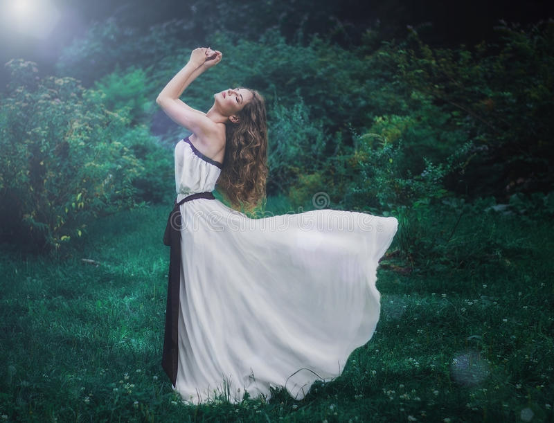 beautiful slender brown-haired young girl with long curly volosvmi in long white dress standing in the middle of a forest royalty free stock image