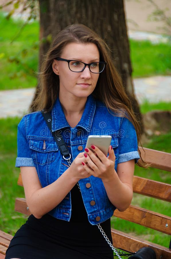 Beautiful slender girl in glasses sits on a bench in the park an royalty free stock photography