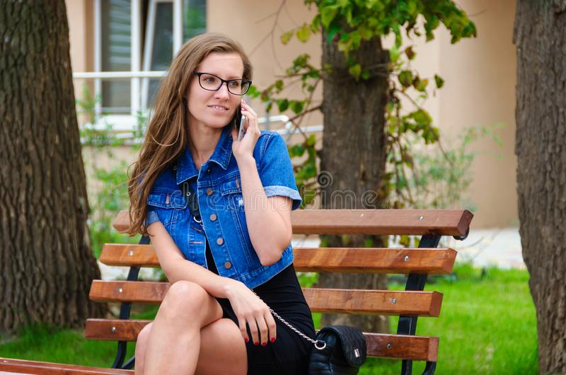 Beautiful slender girl in glasses sits on a bench in the park an stock photos