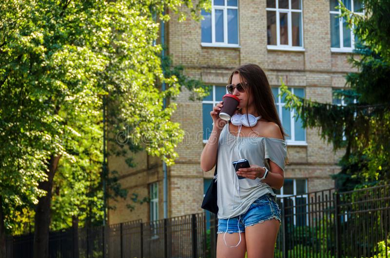 Beautiful stylish girl student drinking coffee on a city street royalty free stock images