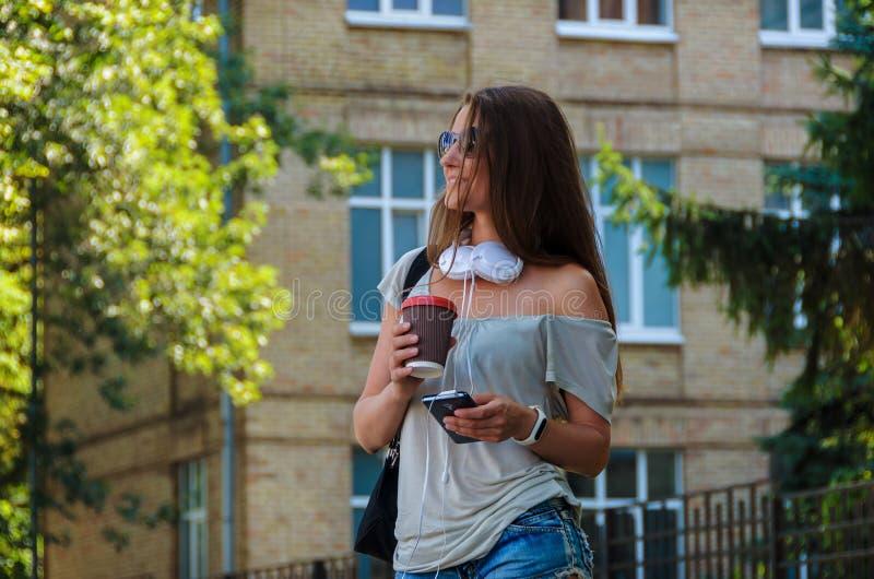 Beautiful stylish girl student drinking coffee on a city street stock photo