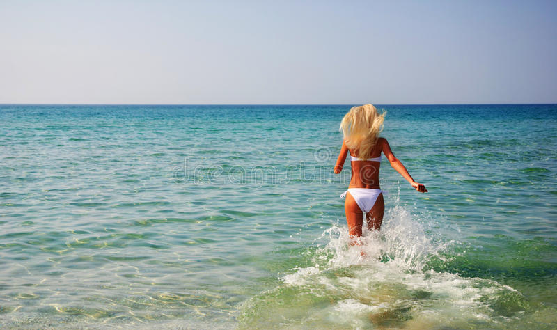 Beautiful slender young woman running in the sea waves royalty free stock photography