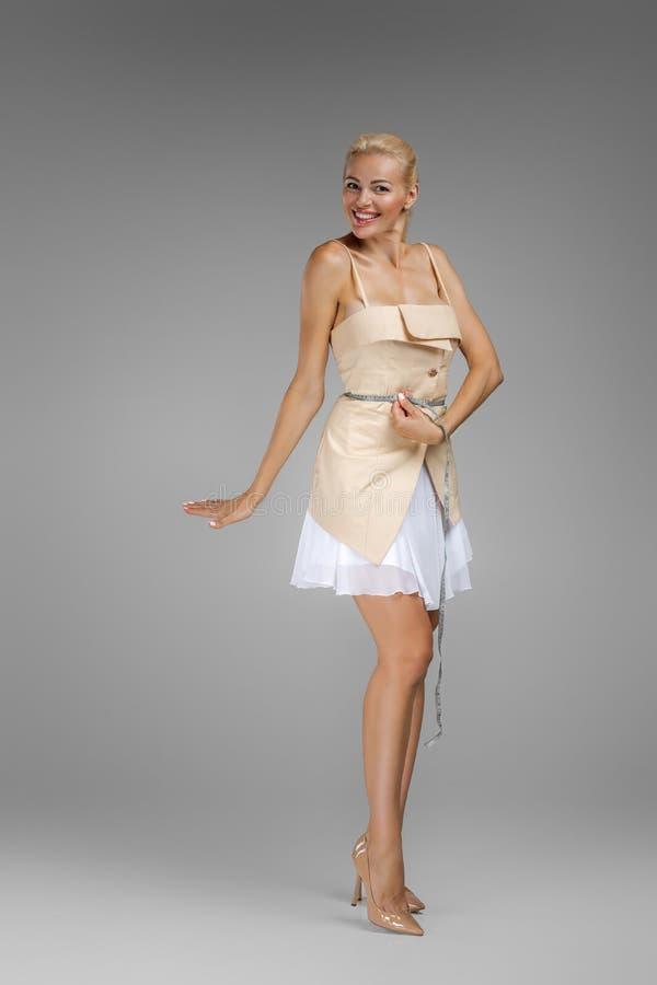 Beautiful slim blond woman holding centimeter measuring stock image