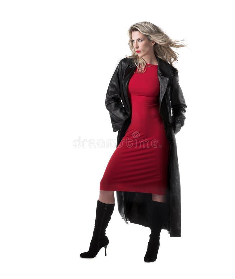 Beautiful,slim blonde woman, red dress, black coat royalty free stock images