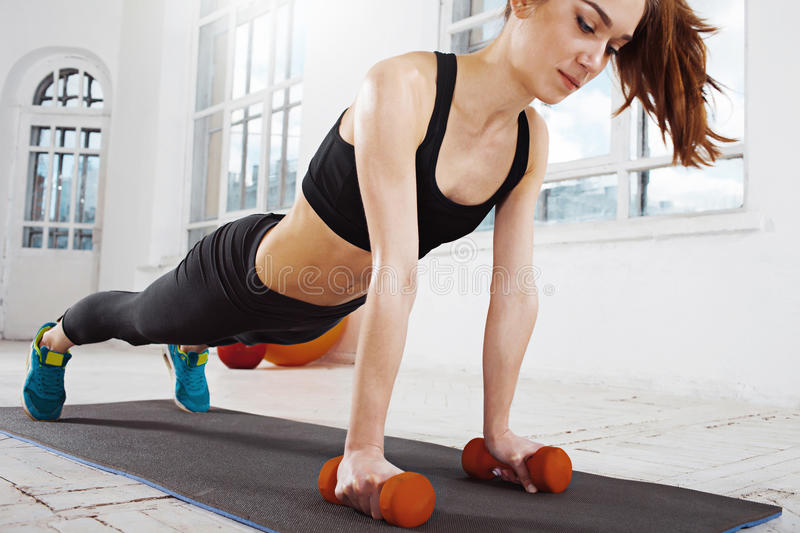 Beautiful slim brunette doing some push ups a the gym royalty free stock image
