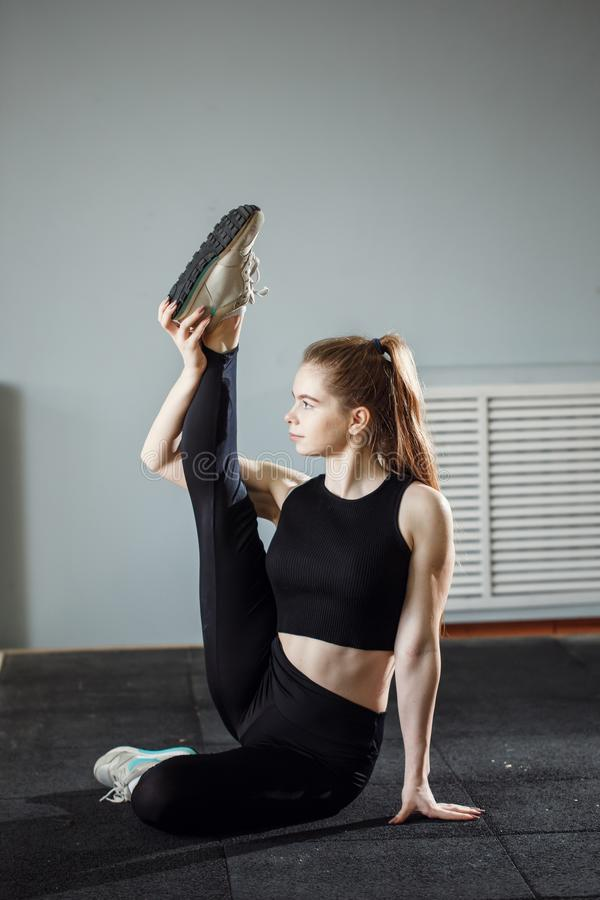 Beautiful slim brunette doing some stretching exercises in a gym stock images
