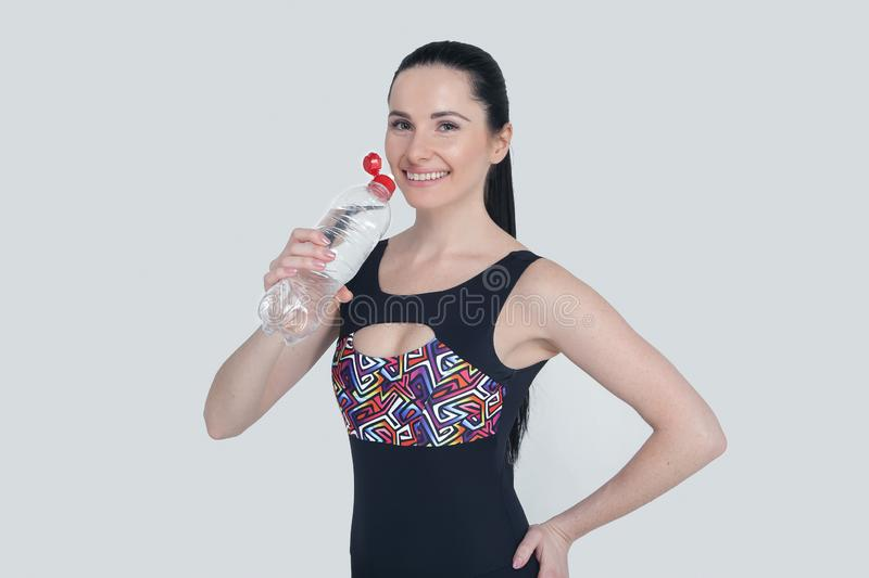 Beautiful slim brunette young girl sports clothes on gray background. Sporty healthy model drinking water from bottle to stay royalty free stock image