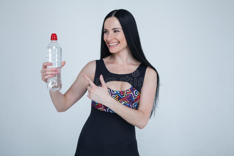 Beautiful slim brunette young girl sports clothes on gray background. Sporty healthy model pointing to a bottle of water. stay stock photos