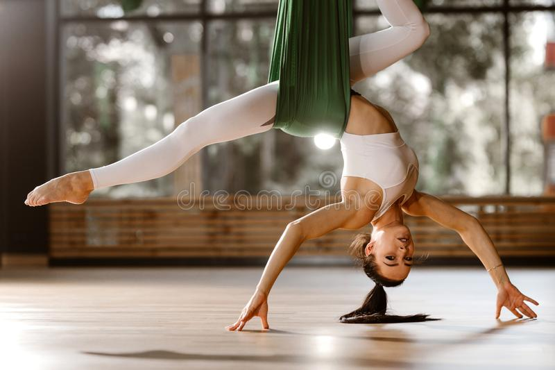 Beautiful slim dark-haired girl dressed in white sports top  and tights is doing stretching exercise on green hammock royalty free stock photos
