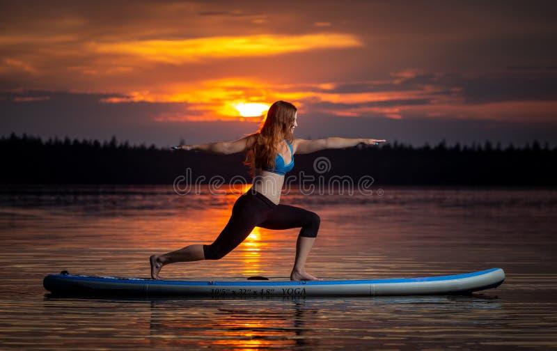 Girl exercising yoga on paddleboard in the sunset on scenic lake Velke Darko royalty free stock images