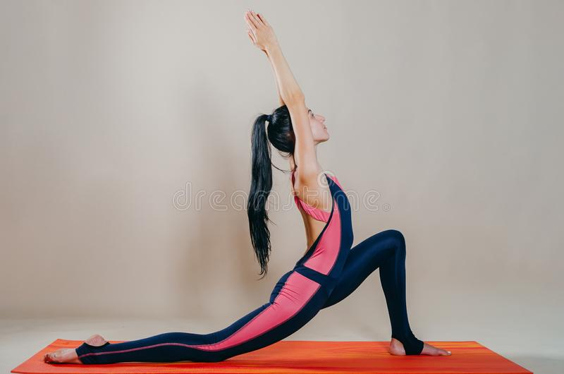 Beautiful slim fit woman coach stands in asanas on a bright rug on a beige background. Yoga practice. Useful hobby for maintaining. A healthy body, wellness stock photography