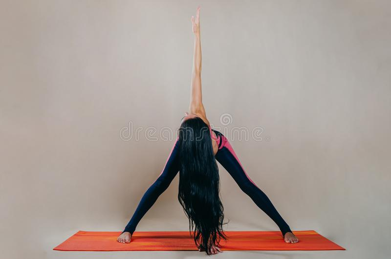 Beautiful slim fit woman coach stands in asanas on a bright rug on a beige background. Yoga practice. Useful hobby for maintaining. A healthy body, wellness royalty free stock photos