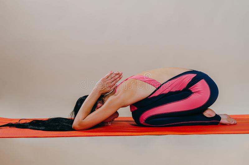 Beautiful slim fit woman coach stands in asanas on a bright rug on a beige background. Yoga practice. Useful hobby for maintaining. A healthy body, wellness royalty free stock image