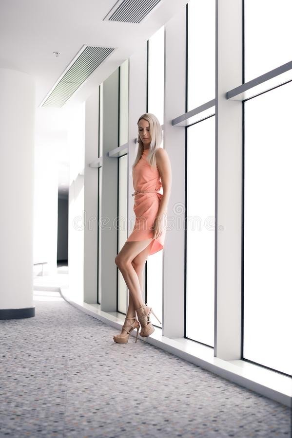 Beautiful slim girl blonde in fashionable pink summer dress in high heels poses at the panoramic windows of office building stock photo