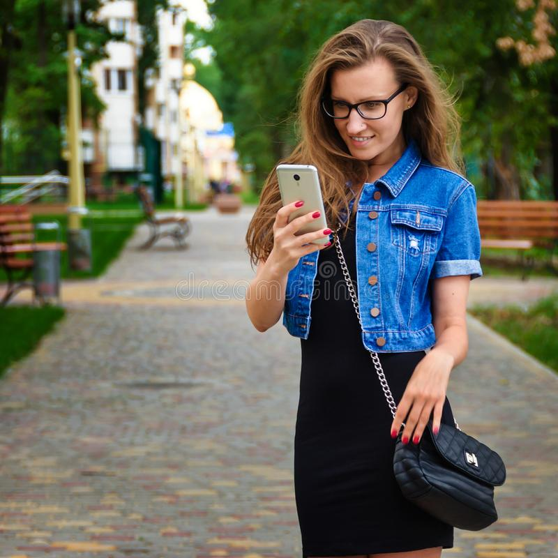 Beautiful slim girl with glasses and a short black dress is stan royalty free stock photo
