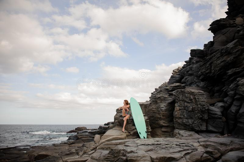 Beautiful slim girl in the multi colored swimsuit sitting near the surf on the rock royalty free stock images