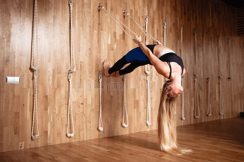 Beautiful slim girl with very long blond hair dressed in a sportswear is doing stretching on special rope equipment in royalty free stock image