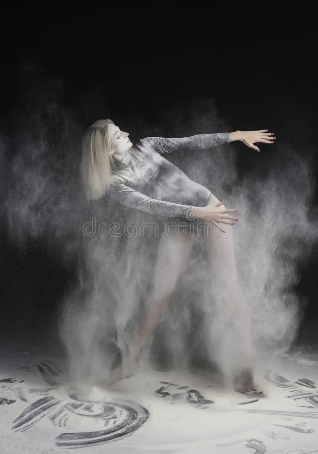 Beautiful slim girl wearing a black gymnastic bodysuit covered with clouds of the flying white powder dances on a dark background stock photo