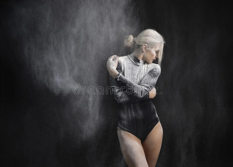 Beautiful slim girl wearing a black gymnastic bodysuit covered with clouds of the flying white powder dances on a dark background stock image