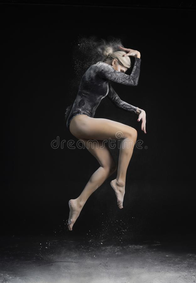 Beautiful slim girl wearing a black gymnastic bodysuit covered with clouds of the flying white powder jumps dancing on a dark. royalty free stock photo