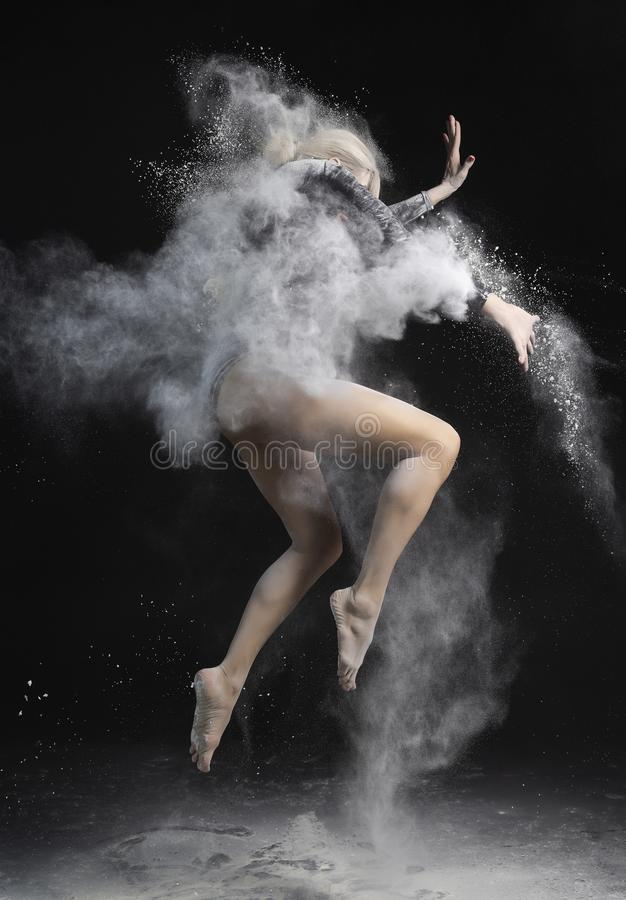 Beautiful slim girl wearing a black gymnastic bodysuit covered with clouds of the flying white powder jumps dancing on a dark. stock images