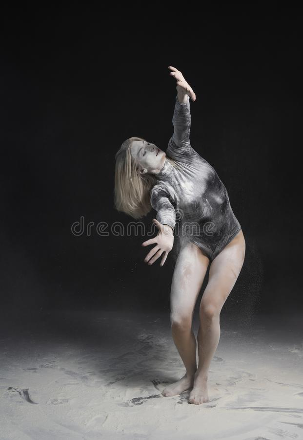 Beautiful slim girl wearing a black gymnastic bodysuit covered with white powder talcum dust jumps dances on a dark. Artistic royalty free stock photos