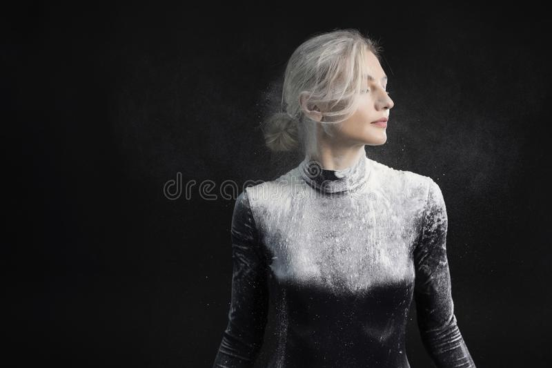 Beautiful slim girl wearing a black gymnastic bodysuit covered with white powder talcum dust jumps dances on a dark. Artistic stock images
