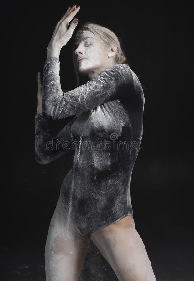 Beautiful slim girl wearing a black gymnastic bodysuit covered with white powder talcum dust jumps dances on a dark. Artistic stock photo