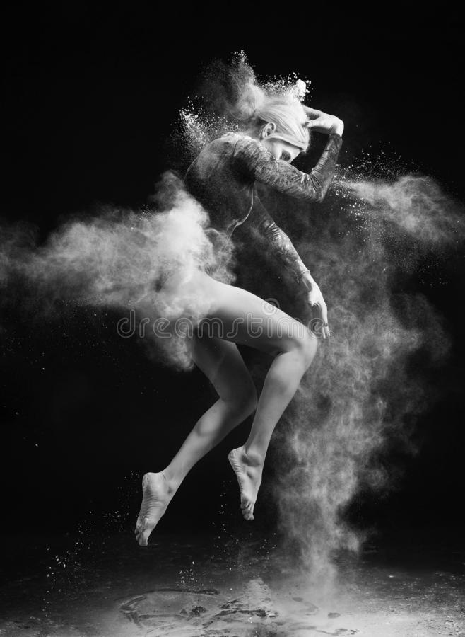 Beautiful slim girl wearing a gymnastic bodysuit covered with clouds of the flying white powder jumps dancing on a dark. Artistic royalty free stock images