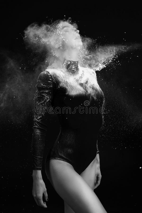 Beautiful slim girl wearing a gymnastic bodysuit covered with clouds of the flying white powder poses on a dark background. royalty free stock image