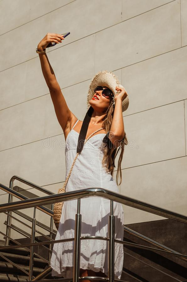 Beautiful slim girl in a white dress and a straw hat takes a selfie on the phone in the city in summer stock photography