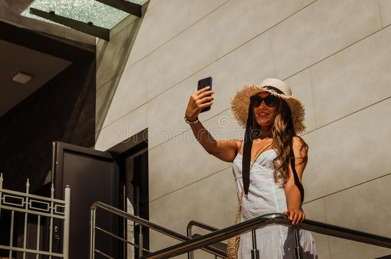 Beautiful slim girl in a white dress and a straw hat takes a selfie on the phone in the city in summer stock photo