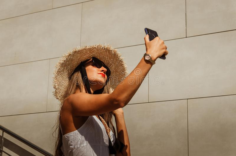 Beautiful slim girl in a white dress and a straw hat takes a selfie on the phone in the city in summer stock images
