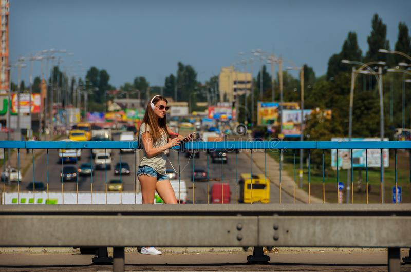 Beautiful stylish girl student stands on the car bridge with a b stock photography