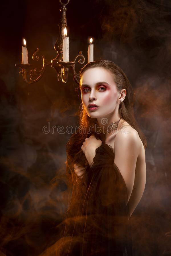 A beautiful slim topless girl, wearing earrings and a necklace, and covering her nudity with a black veil, sensually poses in royalty free stock photos
